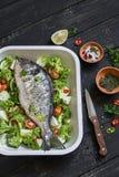Сырцовые ингридиенты - рыбы и овощи Dorado - брокколи, цукини, луки, перцы, известка и специи на темной деревянной поверхности Стоковые Изображения RF