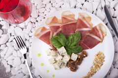Сырцовые и посоленные ветчина, голубой сыр и базилик на белой плите Стекло красного вина и мясного блюда на белом камне Стоковое Фото