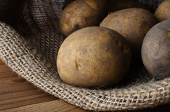 Сырцовые картошки в раскрытом мешке на деревянной таблице Стоковые Изображения RF