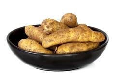 Сырцовые картошки в черном блюде изолированном на белизне Стоковая Фотография RF