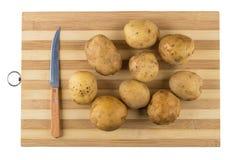 Сырцовые картошки и нож на striped разделочной доске на белизне Стоковые Фотографии RF