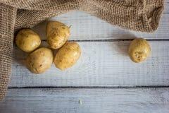Сырцовые картошки на белой деревянной предпосылке Стоковые Изображения
