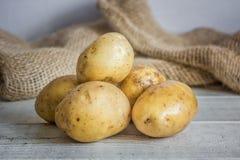 Сырцовые картошки на белой деревянной предпосылке Стоковое Изображение RF