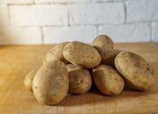Сырцовые картошки на деревянной таблице с солнечным светом утра Стоковые Фотографии RF