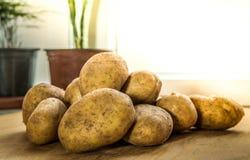 Сырцовые картошки на деревянной таблице с солнечным светом утра Стоковая Фотография RF