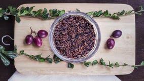 Сырцовые коричневый рис, травы и ягоды на положении квартиры прерывая доски Стоковые Изображения RF