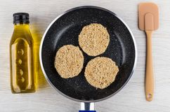 Сырцовые котлеты в сковороде, шпателе, постном масле на таблице Стоковое фото RF