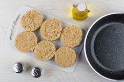 Сырцовые котлеты на разделочной доске, масле, перце, соли, сковороде Стоковые Изображения RF