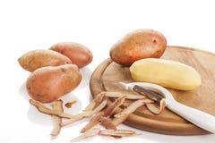 Сырцовые, который слезли картошки на разделочной доске Стоковое фото RF