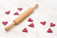 Сырцовые красные в форме сердц печенья на белой таблице с вращающей осью, выпечкой на день валентинки Стоковые Изображения