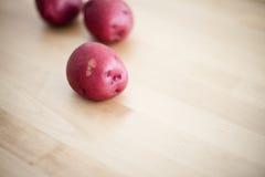 Сырцовые красные картошки на деревянной таблице Стоковые Фотографии RF