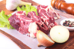Сырцовые края говядины, лист салата, чеснок, точильщик перца и специи на деревянном столе изолированном на белой предпосылке свер Стоковые Изображения
