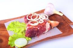 Сырцовые края говядины, лист салата, чеснок, точильщик перца и специи на деревянном столе изолированном на белой предпосылке свер Стоковое Изображение