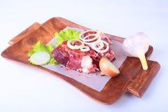 Сырцовые края говядины, лист салата, чеснок, точильщик перца и специи на деревянном столе на белой предпосылке сверху Стоковая Фотография RF
