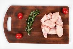 Сырцовые крыла цыпленка на разделочной доске изолированной на белой предпосылке Стоковая Фотография RF