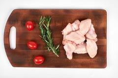 Сырцовые крыла цыпленка на разделочной доске изолированной на белой предпосылке Стоковое Изображение