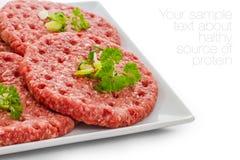 Сырцовые куски гамбургера на белой плите Стоковая Фотография