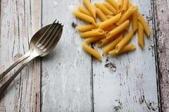 Сырцовые макаронные изделия penne с вилкой и ложка на деревянном столе Стоковое фото RF