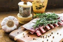 Сырцовые нервюры овечки с розмариновым маслом, перцем, чесноком и маслом на деревянной доске Стоковое Фото