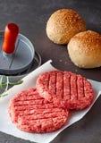 Сырцовые пирожки гамбургера говядины с прессой и Rolls Стоковая Фотография