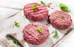 Сырцовые пирожки стейка бургера говяжего фарша на деревянной разделочной доске Стоковое фото RF