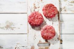 Сырцовые пирожки стейка бургера мяса говяжего фарша на деревянном режа bo Стоковые Фотографии RF