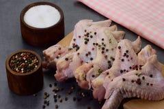 Сырцовые поперченные и посоленные крыла цыпленка на разделочной доске Стоковая Фотография RF