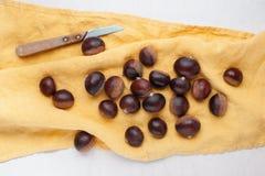 Сырцовые свежие каштаны и кухонный нож Стоковые Изображения