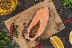 Сырцовые свежие рыбы форели стейка на бумаге, вокруг зеленых цветов, листья, lett Стоковые Фотографии RF