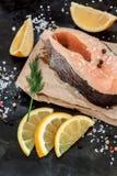Сырцовые свежие рыбы форели стейка на бумаге, вокруг зеленых цветов, листья, lett Стоковая Фотография RF