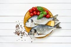 Сырцовые свежие рыбы dorado на желтых плите и овощах на белой таблице Взгляд сверху c Стоковые Изображения RF