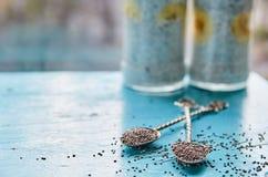 Сырцовые свежие семена chia в 2 винтажных ложках на голубом деревянном столе Здоровый пудинг smoothie chia с свежими бананами Стоковое Изображение