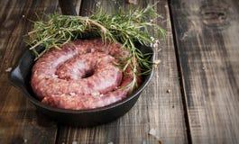 Сырцовые сосиски говядины на лотке чугуна с розмариновым маслом Стоковые Изображения