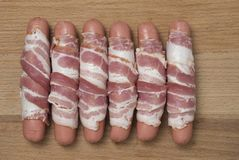 Сырцовые сосиски обернутые в копченом беконе готовом к испеченный Взгляд сверху Стоковая Фотография