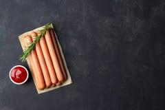 Сырцовые сосиски frankfurter с кетчуп на разделочной доске Взгляд сверху стоковое фото rf