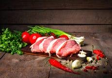 Сырцовые сочные стейки мяса готовые для жарить в духовке на черной доске мела Стоковые Изображения