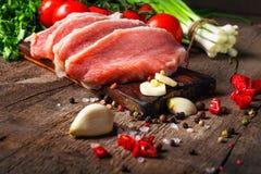 Сырцовые сочные стейки мяса готовые для жарить в духовке на черной доске мела Стоковое фото RF