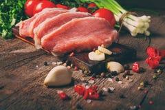 Сырцовые сочные стейки мяса готовые для жарить в духовке на черной доске мела Стоковое Изображение RF