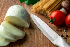 Сырцовые спагетти на деревянной доске с отрезанными моццареллой, свежими овощами, специями и грибами стоковые фото