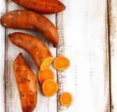 Сырцовые сладкие картофели на деревянной предпосылке Стоковое фото RF