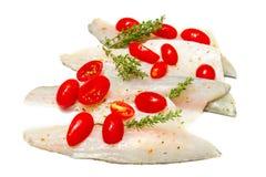 Сырцовые филе морского окуня с томатами вишни на белизне Стоковая Фотография