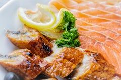 Сырцовые salmon части филе служили с лимоном, черными оливками и травами на белом конце плиты вверх с селективным фокусом Стоковое Изображение