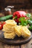 Сырцовый все макаронные изделия uovo `, лапши яичка на темной деревянной деревенской предпосылке Стоковая Фотография