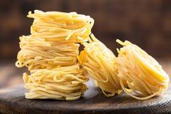 Сырцовый все макаронные изделия uovo `, лапши яичка на темной деревянной деревенской предпосылке Стоковые Изображения