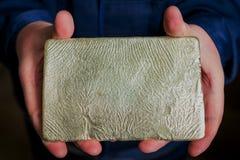 Сырцовый золотой ингот в руках стоковая фотография rf