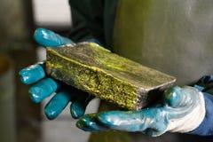 Сырцовый золотой ингот в руках стоковые изображения rf