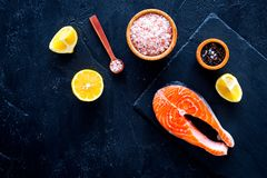 Сырцовый красный стейк рыб Peiece свежих семг на разделочной доске около соли моря, перца, кусков лимона на черной предпосылке по Стоковые Фото