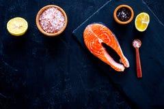 Сырцовый красный стейк рыб Peiece свежих семг на разделочной доске около соли моря, перца, кусков лимона на черной предпосылке по Стоковое Изображение