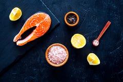 Сырцовый красный стейк рыб Peiece свежих семг на разделочной доске около соли моря, перца, кусков лимона на черной предпосылке по Стоковые Изображения RF