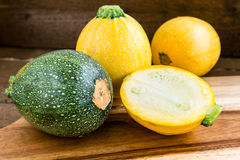 Сырцовый круглый желтый и зеленый цукини и отрезок одно на деревянной предпосылке Стоковое Фото